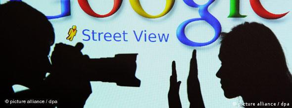 A photographer holds camera to a person holding up both hands signaling no with the Google Street View logo in the background