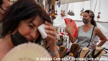 Women cool themselves with fans in the Rastro flea market during a heatwave in Madrid, Spain, Sunday, Aug. 15, 2021. Spain set a new provisional heat record of 47.2 degrees Celsius (116.96 Fahrenheit) on Saturday as Southern Europe sweltered under a relentless summer sun. (AP Photo/Andrea Comas)