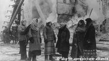 Blockade v.Leningrad 1941/Zerstoerungen.. 2. Weltkrieg / Sowjetunion. Belagerung Leningrads durch die deutsche Heeresgruppe Nord, ab 8.9.1941. - Frauen vor brennenden Truemmern eines Hauses nach einem Angriff.- Foto, Winter 1941.