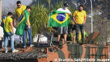 Supporters of Brazilian President Jair Bolsonaro stand on a military vehicle outside the Alvorada Palace, during the Independence Day celebrations in Brasilia, on September 7, 2021. - Fighting record-low poll numbers, a weakening economy and a judiciary he says is stacked against him, President Jair Bolsonaro has called huge rallies for Brazilian independence day Tuesday, seeking to fire up his far-right base. (Photo by EVARISTO SA / AFP) (Photo by EVARISTO SA/AFP via Getty Images)