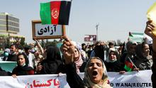 An Afghan woman raises the flag of the former Afghan government as she chants during the anti-Pakistan protest in Kabul, Afghanistan, September 7, 2021. WANA (West Asia News Agency) via REUTERS ATTENTION EDITORS - THIS IMAGE HAS BEEN SUPPLIED BY A THIRD PARTY.