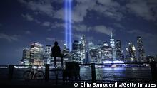 07.09.21 *** NEW YORK, NEW YORK - SEPTEMBER 07: A person watches the Tribute In Light shine into the sky from Lower Manhattan during a test on September 07, 2021 in New York City. Honoring the victims of the September 11, 2001 attack that killed almost 3,000 people at the World Trade Center, the Tribute in Light is a commemorative public art installation that was first presented six months after 9/11 and then every year since on the anniversary. New York City is preparing to mark the 20th anniversary of the September 11 terrorist attacks. (Photo by Chip Somodevilla/Getty Images)