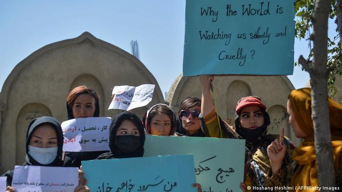 Mulheres afegãs com cartazes
