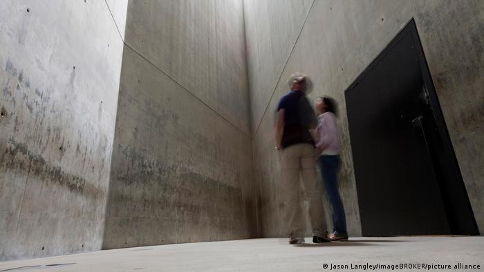 Dos personas paradas frente a la Torre del Holocausto.