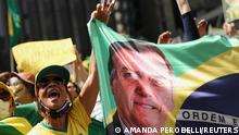 A supporter of far-right President Jair Bolsonaro holds a banner with his image during a march in a show of support for his attacks on the country's Supreme Court, in Sao Paulo, Brazil, September 7, 2021. REUTERS/Amanda Perobelli