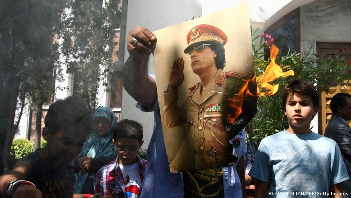 Demonstrators set fire to a poster of Libyan leader Moamer Kadhafi, copies of his Green Book and Libyan flags.