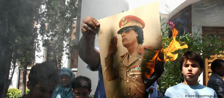 Several people, a house and trees in the background, someone holds up a burning picture of Gadhafi