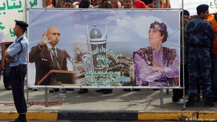 A Libyan policeman stands guard next to a banner bearing portraits of Libyan leader Moammar Ghadafi and son Saif al-Islam.