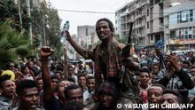 (FILES) In this file photo taken on June 29, 2021 A rebel that is pro-TPLF (Tigray People's Liberation Front) is escorted by people on a street as he returns in Mekele, the capital of Tigray region, Ethiopia, on June 29, 2021. - Rebels from Ethiopia's war-hit Tigray killed at least 125 residents of a village in the neighbouring Amhara region earlier this month before being driven out by pro-government forces, doctors said on September 8, 2021. There were 125 dead in Chenna village... I saw the mass grave myself, Mulugeta Melesa, head of the hospital in nearby Dabat town, told AFP, adding that residents were still searching for dead bodies around the area and counting is still going on. (Photo by Yasuyoshi Chiba / AFP)