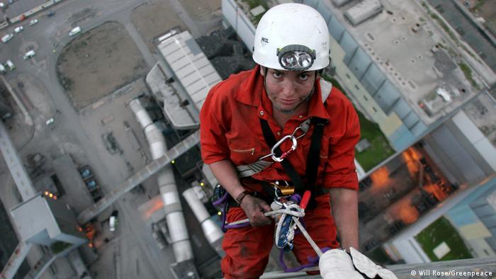 Активистка поднимается на вершину трубы угольной электростанции