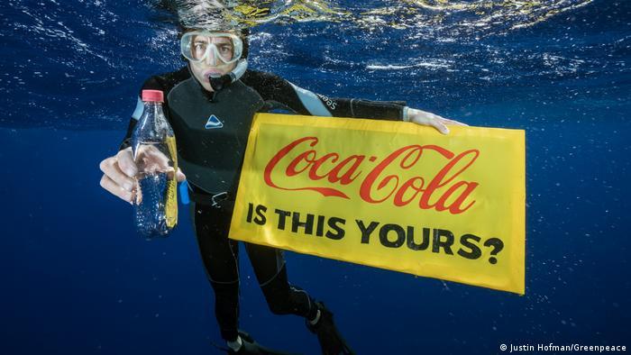 В руках активиста под водой транспарант и бутылка из под Кока-Колы
