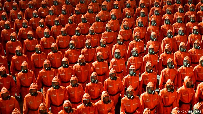 Personnel in orange hazmat suits march during a paramilitary parade held to mark the 73rd founding anniversary of the republic at Kim Il Sung square in Pyongyang in this undated image supplied by North Korea's Korean Central News Agency on September 9, 2021
