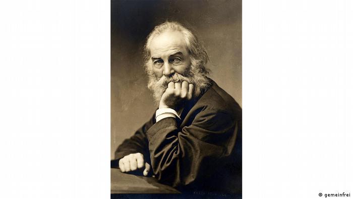 Walt Whitman sitzt mit Bart am Tisch und stützt mit seiner linken Hand den Kopf auf (schwarz-weiß Fotografie)