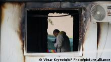 A forensic officer works at the site after a fire at a makeshift hospital, in North Macedonia's northwestern city of Tetovo, early Thursday, Sept. 9, 2021. The government of North Macedonia will hold an emergency meeting over a fire overnight that ripped through a field hospital set up to treat COVID-19 patients, leaving 14 people dead. The blaze broke out late Wednesday in the western city of Tetovo, where the hospital had been set up following a recent spike in infections in the region that left local hospitals full. (AP Photo/Visar Kryeziu)