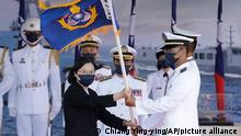 9.9.2021, Yilan county, Taiwan, Taiwan's President Tsai Ing-wen, left, presents a flag during the commissioning ceremony of the the domestically made Ta Jiang warship at the Suao naval base in Yilan county, Taiwan, Thursday, Sept. 9, 2021. Taiwan's president oversaw the commissioning of a new domestically made navy warship Thursday as part of the island's plan to boost indigenous defense capacity amid heightened tensions with China. (AP Photo/Chiang Ying-ying)