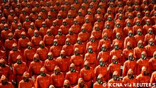 Personnel in orange hazmat suits march during a paramilitary parade held to mark the 73rd founding anniversary of the republic at Kim Il Sung square in Pyongyang in this undated image supplied by North Korea's Korean Central News Agency on September 9, 2021. KCNA via REUTERS ATTENTION EDITORS - THIS IMAGE WAS PROVIDED BY A THIRD PARTY. REUTERS IS UNABLE TO INDEPENDENTLY VERIFY THIS IMAGE. NO THIRD PARTY SALES. SOUTH KOREA OUT. NO COMMERCIAL OR EDITORIAL SALES IN SOUTH KOREA. TPX IMAGES OF THE DAY