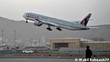 A Qatari security personnel stands guard as a Qatar Airways aircraft takes off from the airport in Kabul on September 9, 2021. - Some 200 passengers, including US citizens, left Kabul airport on September 9, 2021, on the first flight carrying foreigners out of the Afghan capital since a US-led evacuation ended on August 30. (Photo by WAKIL KOHSAR / AFP)