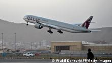 A Qatari security personnel stands guard as a Qatar Airways aircraft takes off from the airport in Kabul on September 9, 2021. - Some 200 passengers, including US citizens, left Kabul airport on September 9, 2021, on the first flight carrying foreigners out of the Afghan capital since a US-led evacuation ended on August 30. (Photo by WAKIL KOHSAR / AFP) (Photo by WAKIL KOHSAR/AFP via Getty Images)