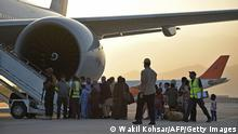 Passengers prepare to board a Qatar Airways aircraft at the airport in Kabul on September 9, 2021. - Some 200 passengers, including US citizens, left Kabul airport on September 9, 2021, on the first flight carrying foreigners out of the Afghan capital since a US-led evacuation ended on August 30. (Photo by WAKIL KOHSAR / AFP) (Photo by WAKIL KOHSAR/AFP via Getty Images)