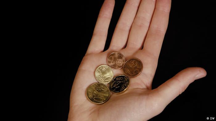 Hand mit €0,087 in Euro-Münzen