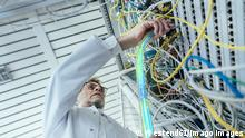 Mature male IT support plugging in fiber optic cable at data center model released Symbolfoto property released LIFIF00013