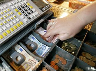 Hand reaching into cash register for bills