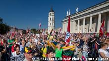 Anti-vaccination protesters waving national flags take part in a protest at Cathedral Square in Vilnius, Lithuania, Friday, Sept. 10, 2021, against the government's restrictions for people who have not developed immunity to COVID-19. (AP Photo/Mindaugas Kulbis)