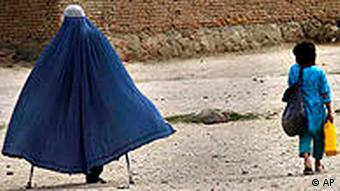 An Afghan girl carries the ration of her mother, a victim of land mines and a war widow after receiving them from CARE's food distribution program for windows in Kabul, Afghanistan, Thursday, April 15, 2010. (AP Photo/Dar Yasin)
