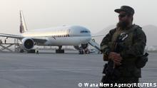 A member of Taliban security forces stands guard in front of a Qatar Airways airplane boarding passengers at the international airport in Kabul, Afghanistan, September 10, 2021. WANA (West Asia News Agency) via REUTERS ATTENTION EDITORS - THIS IMAGE HAS BEEN SUPPLIED BY A THIRD PARTY.