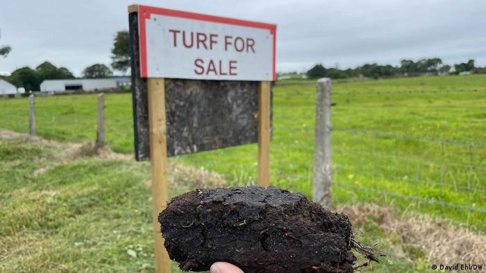 A signpost in a field advertising a place to buy turf