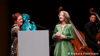 Oberbürgermeisterin Dörner hält die blaue Kunstfigur in den Händen und überreicht sie Nikel Wagner.
