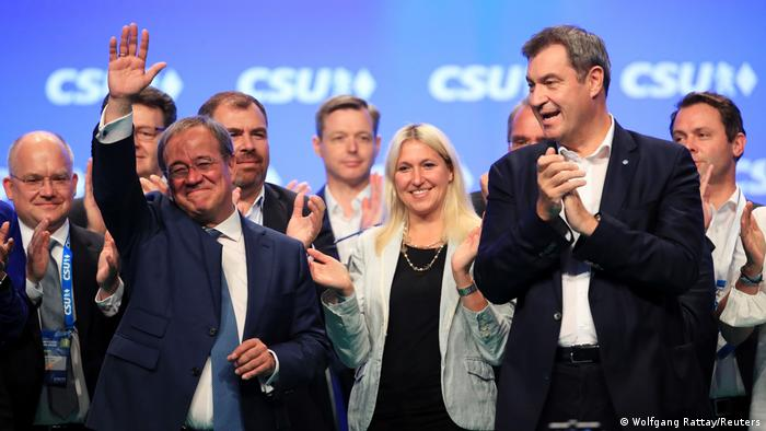 Armin Laschet on a stage waving and Markus Söder clapping