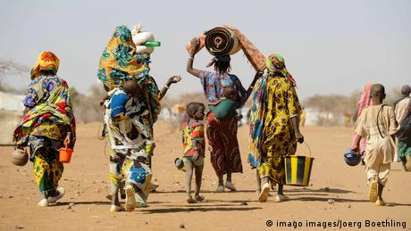 Women, children in colorful clothing walk in arid landscape, view from behind
