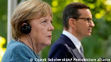 German Chancellor Angela Merkel, left, and Poland's Prime Minister Mateusz Morawiecki give a press conference in Warsaw, Poland, Saturday, Sept.11, 2021.Merkel is visiting the Polish capital Morawiecki at a time when Poland faces migration pressure on its eastern border with Belarus. (AP Photo/Czarek Sokolowski)