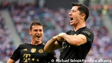 Bayern's Robert Lewandowski, right, celebrates after scoring the first goal of the match, on a penalty, during the German Bundesliga soccer match between RB Leipzig and FC Bayern Munich in Leipzig, Germany, Saturday, Sept. 11, 2021. (AP Photo/Michael Sohn)