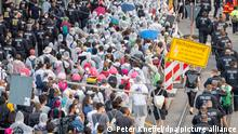 10.09.2021, Bayern, München: Protestteilnehmer in weißen Ganzkörperanzügen gehen von Polizei begleitet über eine Straße, um gegen die Automesse IAA-Mobility zu demonstrieren. Foto: Peter Kneffel/dpa +++ dpa-Bildfunk +++