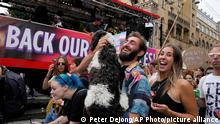 A person carries a dog when dancing alongside a truck reading Give Us Back Our Safe Spaces during a protest of organizers and fans of music festivals stage against the government's COVID-19 restrictions on large-scale outdoor events in Amsterdam, Netherlands, Saturday, Sept. 11, 2021. On Saturday, the festivals came to music fans as hundreds of performers and festival organizers called again for demonstration marches through Dutch cities to protest what they argue are unfair restrictions that have forced the cancellation of summer festivals and other events. (AP Photo/Peter Dejong)