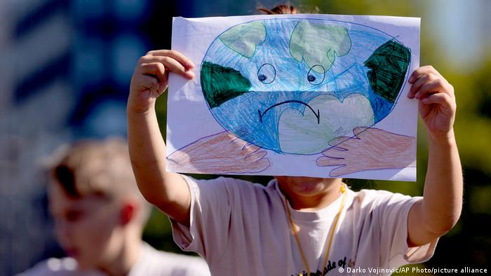 A girl holds a drawing of the Earth during the protest