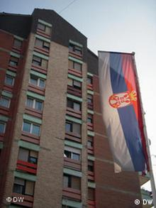 Serbian flag flies in front of an apartment block in Mitrovica