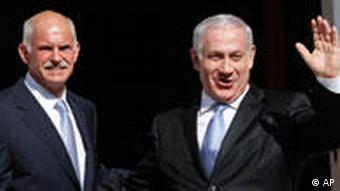 Israeli Prime Minister Benjamin Netanyahu, right, gestures to photographers as he is welcomed by his Greek counterpart George Papandreou, in Athens