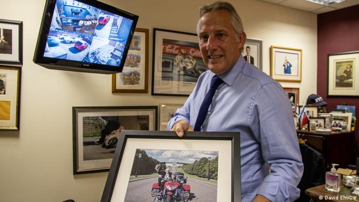 Ian Paisley Jr., holds up a framed photo