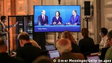 BERLIN, GERMANY - SEPTEMBER 12: Journalists watch the 2nd Triell televised debate with chancellor candidates (L-R) SPD Chancellor candidate Olaf Scholz, Annalena Baerbock, co-leader of Germany's Green party and Armin Laschet, leader of the German Christian Democrats (CDU) on screen on September 12, 2021 in Berlin, Germany. Laschet, Olaf Scholz of the Social Democrats (SPD) and Annalena Baerbock of the Greens Party, who are the three leading candidates to succeed outgoing chancellor Angela Merkel, are participating in the debate ahead of federal parliamentary elections scheduled for September 26. (Photo by Omer Messinger/Getty Images)