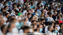 Soccer supporters attend the the Spanish La Liga soccer match between Real Madrid and Celta de Vigo at the Bernabeu stadium in Madrid, Spain, Sunday, Sept. 12, 2021. (AP Photo/Manu Fernandez)