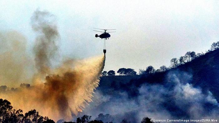 A helicopter is dropping water on burning trees in Sierra Bermeja, Spain