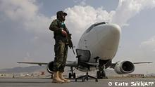 A Taliban fighter stands guard next to an Ariana Afghan Airlines aircraft on the tarmac at the airport in Kabul on September 12, 2021. (Photo by Karim SAHIB / AFP)