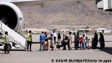 13.09.2021 *** Passengers stand in a queue to board on a Pakistan International Airlines plane, which is the first international commercial flight to land since the Taliban retook power in Afghanistan on August 15, at the airport in Kabul on September 13, 2021. (Photo by Karim SAHIB / AFP) (Photo by KARIM SAHIB/AFP via Getty Images)