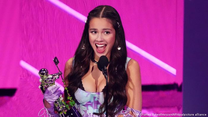 Olivia Rodrigo holds a Moon Person award, smiling.