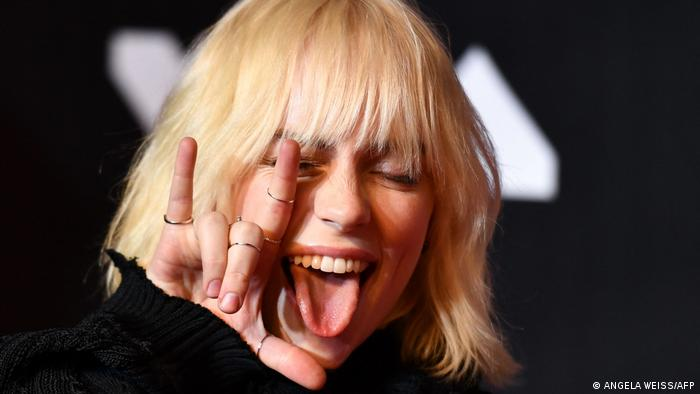 Billie Eilish, woman with blond hair sticks out her tongue and makes a hand sign