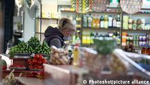 KYIV, UKRAINE - MAY 8, 2020 - A vendor in a face mask is seen behind a vegetable stall at the Volodymyrskyi market that has reopened amid the easing of lockdown, Kyiv, capital of Ukraine.