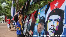 A vendor sells T-shirts promoting Nicaraguan President Daniel Ortega and The Sandinista National Liberation Front ruling party on the sidelines of a new monument, called the Peace Bell, before its inauguration ceremony later in the day in Managua, Nicaragua, Friday, July 17, 2020. Nicaraguan President Daniel Ortega's government is being deterred by the new coronavirus from holding the usual mass celebration to mark the victory of the country's revolution July 19, and will instead unveil a new addition to its collection of monuments. At right is a T-shirt of Cuba's revolutionary hero Ernesto Che Guevara. (AP Photo/Alfredo Zuniga)